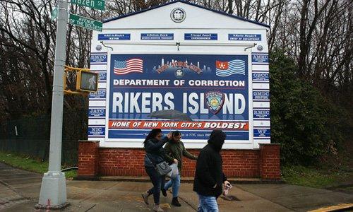 2 women walking across the Rikers Island sign