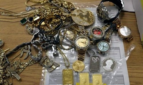 a bunch of gold watches and gold chains on a table