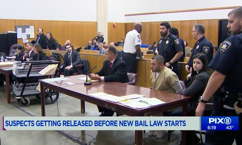 a court room with police offers and defendant in handcuffs