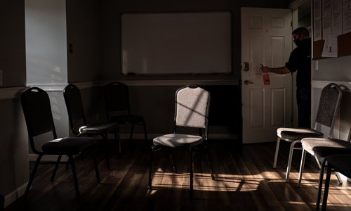 dark room with white board and chairs and a guy with a mask and sanitizer